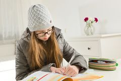 Teenaged girl going homework in hard condition - heating is not working during winter time stock image
