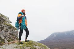 Hipster-climber stands in a down jacket on a rock with a rope on his shoulder Stock Photos
