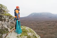 Hipster-climber stands in a down jacket on a rock with a rope on his shoulder Royalty Free Stock Photo
