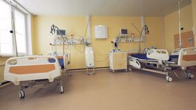 Fully-equipped hospital ward with two wheeled beds and medical inventory stock footage
