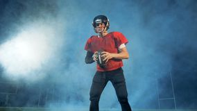 Fully-equipped male american football player in clouds of smoke stock footage