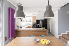 Fully-equipped modern kitchen interior. With an oven, large, black refrigerator, and a long, purple radiator stock images