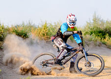 Fully Equipped Professional Downhill Cyclist Riding the Bike on the Dusty Trail. Extreme Sports Royalty Free Stock Photo