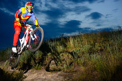 Fully Equipped Professional Downhill Cyclist Riding the Bike on the Night Rocky Trail Stock Image