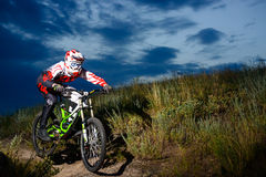 Fully Equipped Professional Downhill Cyclist Riding the Bike on the Night Rocky Trail Royalty Free Stock Photo