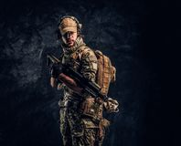 Fully equipped soldier in camouflage uniform holding an assault rifle. Studio photo against a dark wall. Fully equipped soldier in camouflage uniform holding an stock photos