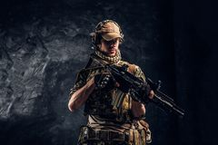 Fully equipped soldier in camouflage uniform holding an assault rifle. Studio photo against a dark wall. Fully equipped soldier in camouflage uniform holding an stock image