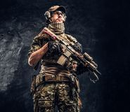 Fully equipped soldier in camouflage uniform holding an assault rifle. Studio photo against a dark wall. Fully equipped soldier in camouflage uniform holding an stock photography