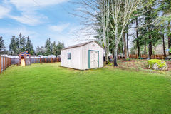 Fully fenced grass filled  backyard with lots of space. Fully fenced grass filled backyard with lots of space includes large shed, patio and playground for Royalty Free Stock Image