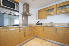 Fully fitted modern kitchen. In birch wood finish with modern appliances stock photography