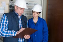 Fully-fledged electrician and female apprentice. Female Stock Photography