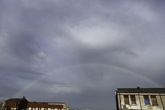 Fully formed rainbow over buildings. In city Stock Photography