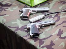 Fully loaded magnum guns ready to shoot on army soldier uniform tablecloth background in shooting range. Sport, Recreation, Game, stock photography