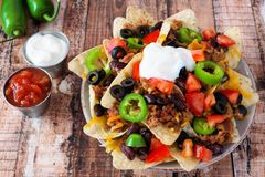Fully loaded Mexican nacho chips on rustic wood background Stock Photography