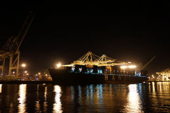Fully loaded Shipping Cargo Boat unloaded at night. OAKLAND - OCTOBER 12: Fully loaded Hanji Shipping Cargo Boat unloaded at night under giants unloading cranes Royalty Free Stock Image