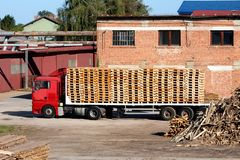 Fully loaded truck trailer with wooden pallets surrounded with wooden boards and factory buildings at abandoned industrial complex. On warm sunny day stock image