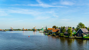 Fully operational historic Dutch Windmills and houses along the Zaan River Royalty Free Stock Images