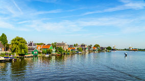 Fully operational historic Dutch Windmills and houses along the Zaan River Stock Images