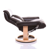 Fully reclined luxurious leather recliner chair. A chocolate coloured leather recliner chair with light wooden base, show side on in fully reclined position Royalty Free Stock Photos
