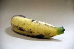 Fully ripe of one banana isolated on brown background. it is a long curved fruit that grows in clusters and has soft pulpy flesh. Fully ripe of one banana Stock Photos