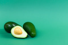 Fully ripened avocado on a green background. Fully ripened contrast avocado on a green background Royalty Free Stock Images