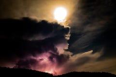 Fulmine dietro la montagna alla notte fotografia stock libera da diritti