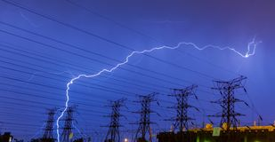Fulmine sulle linee elettriche di elettricità e sulla sotto stazione immagine stock libera da diritti