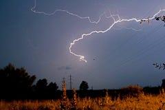 Fulmine velocemente su una notte di estate tempestosa Un campo con i pali ed i cavi elettrici immagini stock libere da diritti