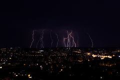 Fulmini multipli sopra una grande città di notte Fotografia Stock