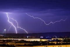 Fulmini sopra la città nella notte immagini stock libere da diritti