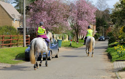 Fulwell Road, Finmere, Oxfordshire, United Kingdom, March 26, 20. 17: Female riders and horses on village road wearing Please Pass Wide & Slow sign on Stock Photo