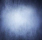 Fumée bleue lumineuse au-dessus de fond noir Images libres de droits