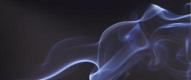 Fumée bleue sur le fond noir Images libres de droits