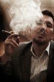 Fumée d'homme à la maison Photo stock
