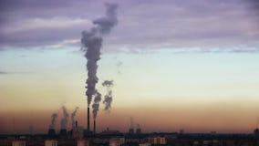 Fumée de cheminées de centrale au-dessus de la ville la nuit banque de vidéos