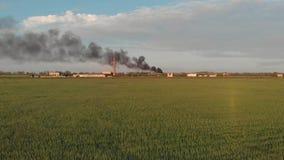 Fumée noire énorme d'un feu dans l'endroit abandonné avec le grand tube de brique rouge clips vidéos