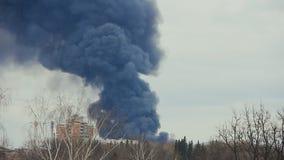 Fumée noire d'un grand feu dans la ville banque de vidéos