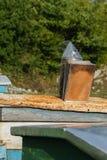 Fumador de la abeja sobre la caja de la abeja Imágenes de archivo libres de regalías