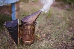 Fumador de la apicultura en la colmena de la abeja Conseguir la miel de la colmena Foto de archivo