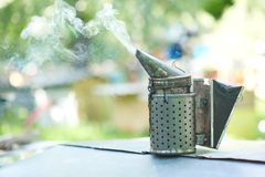 Fumador pasado de moda de la abeja del metal en el colmenar Imagenes de archivo