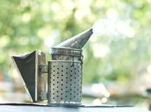 Fumador pasado de moda de la abeja del metal en el colmenar Foto de archivo