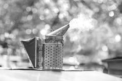 Fumador pasado de moda de la abeja del metal en el colmenar Foto de archivo libre de regalías