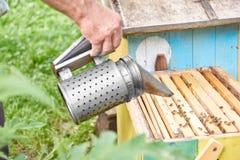Fumador pasado de moda de la abeja del metal en el colmenar Imagen de archivo