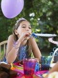 Fumador que sopla de la muchacha en la fiesta de cumpleaños Foto de archivo libre de regalías