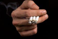Fumador que sostiene tres cigarrillos Fotografía de archivo libre de regalías