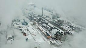 Fumaioli della fabbrica che cuociono a vapore e che fumano nell'inverno freddo, vista aerea strabiliante video d archivio