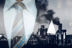 fumaiolo di doppia esposizione nell'inquinamento della fabbrica con l'uomo di affari fotografia stock libera da diritti