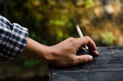Fumando nelle mani degli uomini Immagine Stock