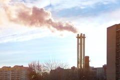 Fumando uma tubulação das plantas de aquecimento que fornecem o calor à cidade e ao céu azul foto de stock royalty free