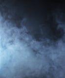Fumée bleu-clair sur un fond noir Photographie stock libre de droits